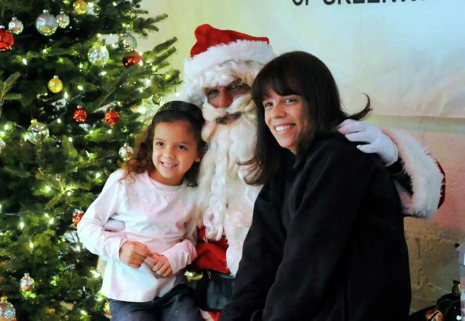 Starla Tejada, 6, left, of Greenwich, and her mother Leticia sit next to Santa during the Boys & Girls Club of Greenwich pancake breakfast with Santa at the club Saturday morning, Dec. 11, 2010.  Starla asked Santa for an iPod Touch. Photo: Bob Luckey / Greenwich Time