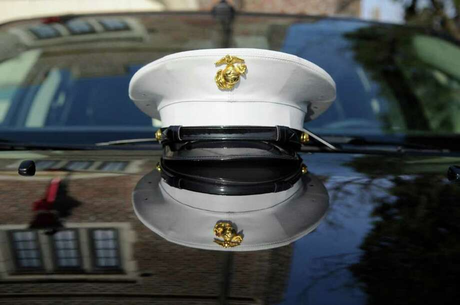 The hat of U.S. Marine Staff Sgt. Heber A. Meraz of the 6th Motor Battalion out of New Haven, is reflected on the hood of a car during the U.S. Marine Corps Toys for Tots drive at the Cos Cob Firehouse, Saturday morning, Dec. 11, 2010. Photo: Bob Luckey / Greenwich Time