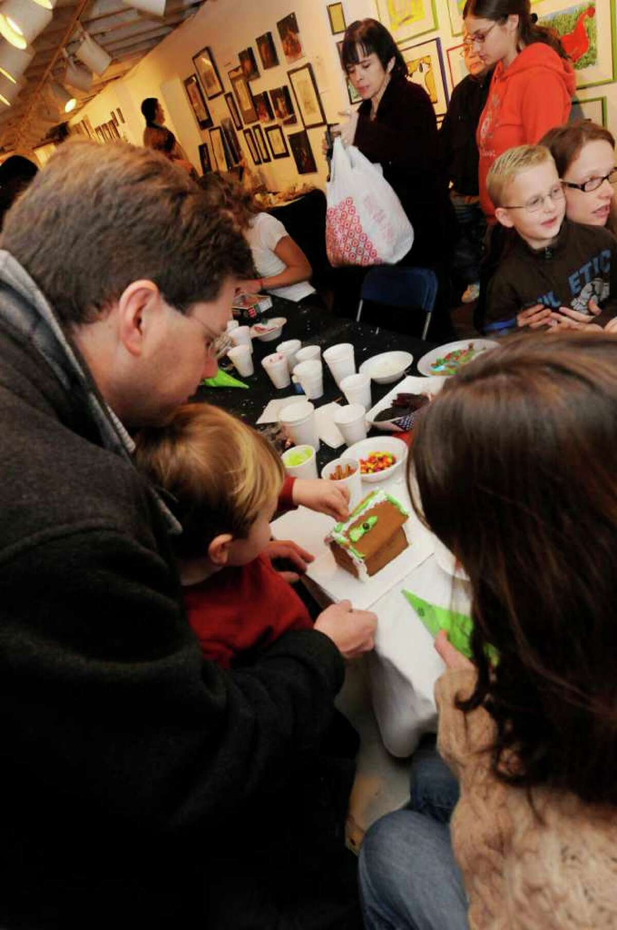 Steve Gagne his wife Kate Molloney and their 3-year-old son Andrew Gagne make gingerbread houses at the Upstate Artist Guild during the annual Winter WonderLark in Albany on Dec. 11. ( Michael P. Farrell/Times Union )
