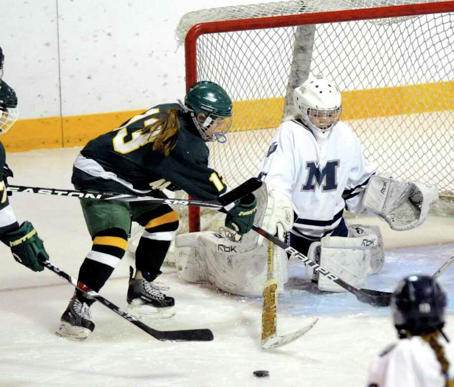 Eva Rosencrans of Greenwich Academy, # 13, left, tries to play the rebound as MIllbrook School goalie, Melissa Rome, #30, clears the puck during girls ice hockey game between Greenwich Academy vs. Millbrook School, at Greenwich Academy, Saturday afternoon, Dec. 11, 2010. Photo: Bob Luckey / Greenwich Time