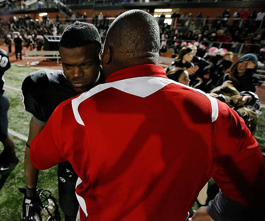 Steele's Malcolm Brown (left) sheds tears of joy as he gets congratulated by a Houston Memorial coach. Kin Man Hui/kmhui@express-news.net Photo: Express-News