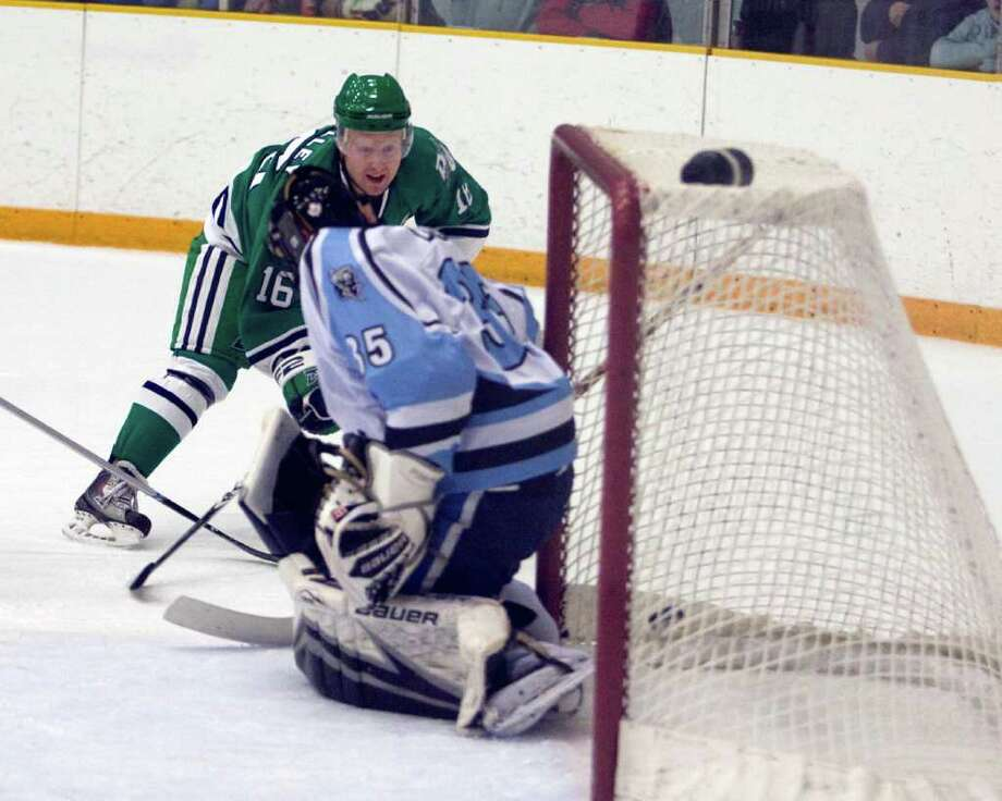 The Whalers' Sean O'Malley (16) puts the puck into the net behind Rome goalie Shane Davis Saturday night at the Danbury Arena. Photo: Barry Horn / The News-Times Freelance
