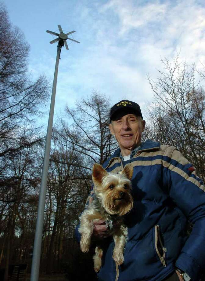 Henry D. Rotman poses with his dog Harley Davidson, behind his house in Milford, Conn. on Tuesday December 7, 2010, in front of the small wind turbine he constructed to generate electric power in 1985. Rotman sucessfully used the power to charge a series of gel batteries used for a diving project. As a former UI engineer, he doubts wind power will work well in Connecticut, due to the unpredictability of the wind here and its lack of sustained strength. Photo: Christian Abraham / Connecticut Post