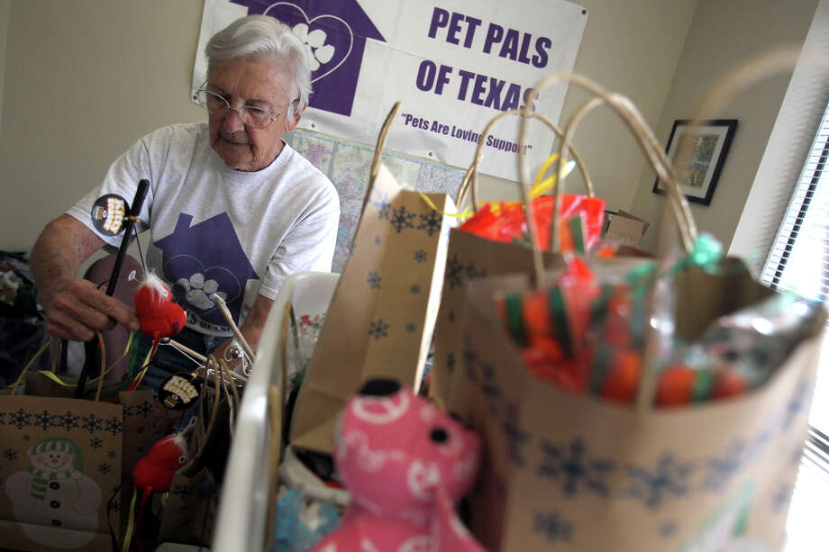 Loyce Jurney, mother of founder Vicki Jurney-Taylor, organizes holiday gift packages for the pets that Pet Pals of Texas cares for at the charity's food bank. Volunteers walk dogs, clean litter boxes and bird cages, and deliver food and medication. Photo: Jennifer Whitney/Special To The Express-News