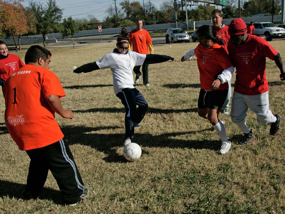 UTSA women's soccer player Stephanie Ogilvie (in white shirt), who helped by coaching and refereeing, attempts a shot on goal surrounded by Haven for Hope residents at Eduardo Garcia Park, next to the homeless center. Photo: J. Michael Short/Special To The Express-News