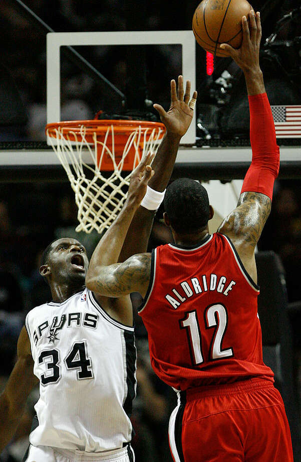 The Spurs' Antonio McDyess goes up to block a shot against the Trail Blazers' LaMarcus Aldridge on Sunday. Photo: MICHAEL MILLER/mmiller@express-news.net