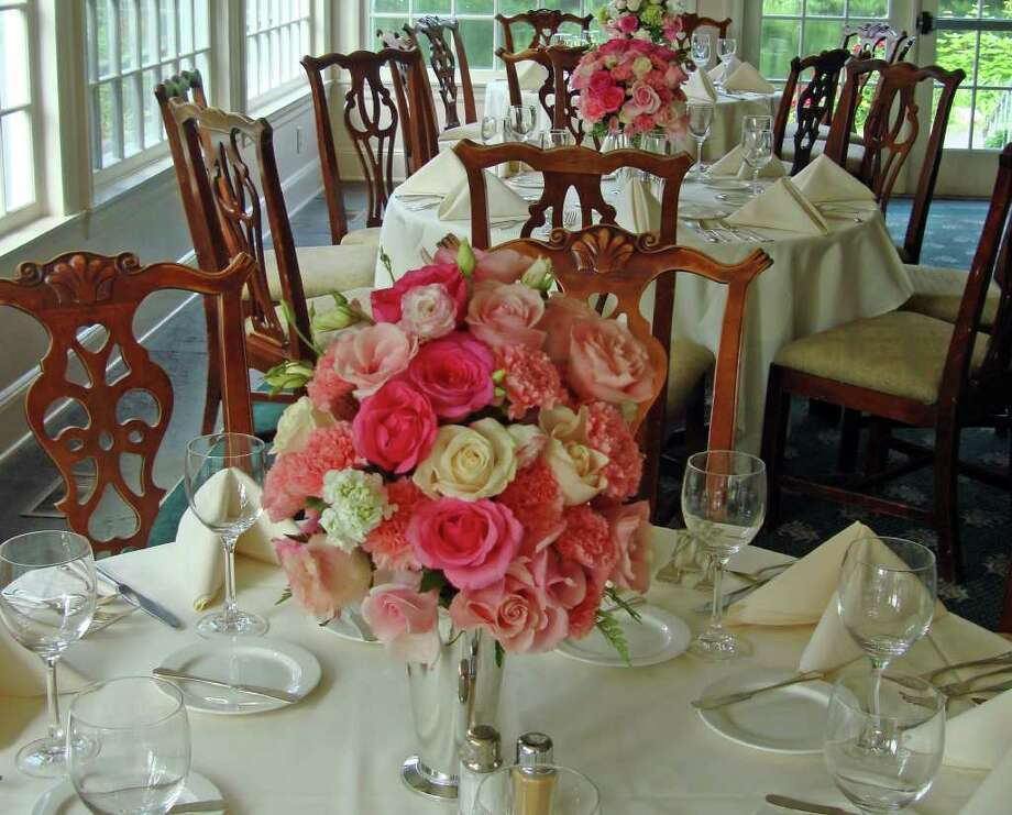 Rose and carnation centerpieces created by Christina Donigian, owner of Christina's Floral Designs, a home-based business in Monroe. Photo: Contributed Photo / Connecticut Post Contributed