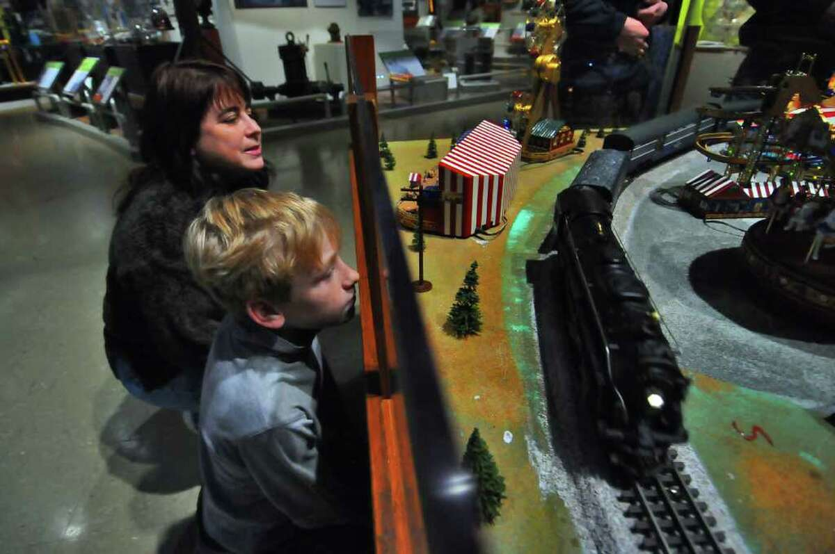 Scott Peterson, 11, and his mother, Alyse, watch a reproduction of a steam engine haul cars around a display built by Upstate Train Associates, at the Schenectady Museum on Sunday, Dec. 12, 2010. (Philip Kamrass / Times Union)