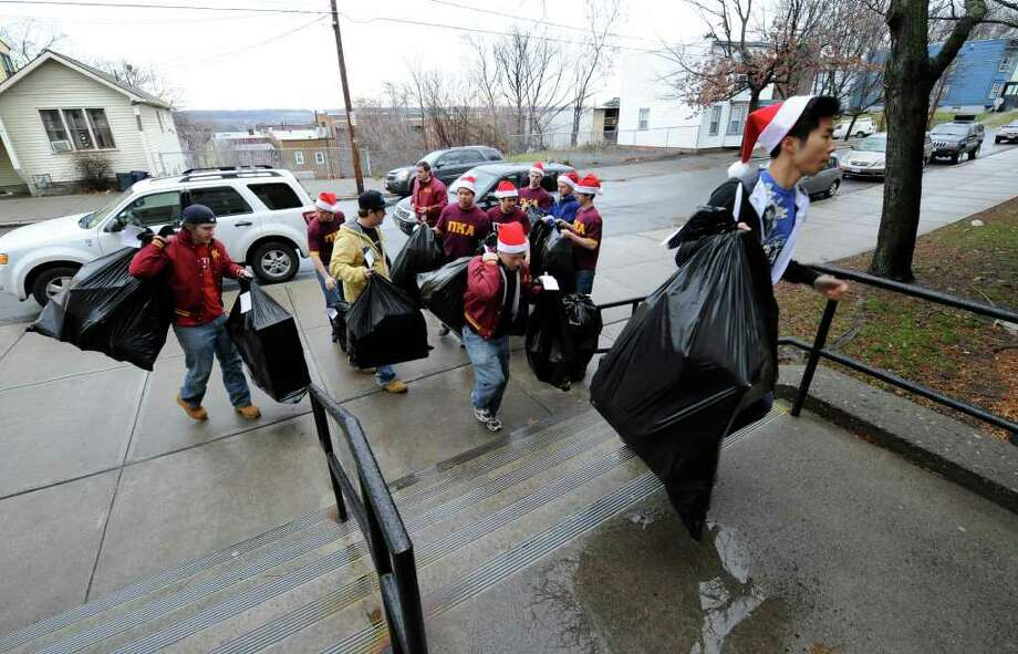 Members of the Pi Kappa Alpha fraternity from RPI bring gifts to the students of Troy's Public School 2 on December 13, 2010. (Skip Dickstein / Times Union) Photo: SKIP DICKSTEIN / 00011385A