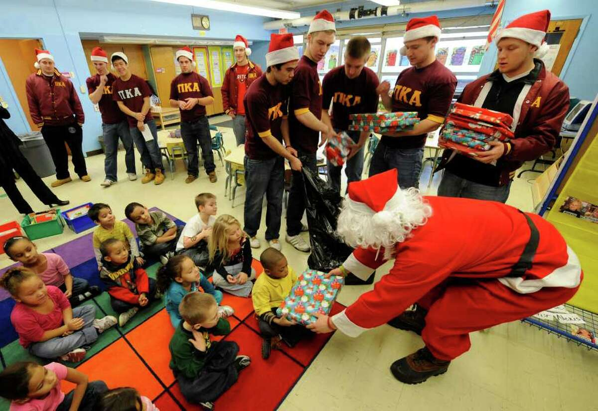 """""""Santa,"""" played by Greg Vernon, with members of the Pi Kappa Alpha fraternity from RPI take gifts to the students of Troy's Public School 2 on December 13, 2010. (Skip Dickstein / Times Union)"""