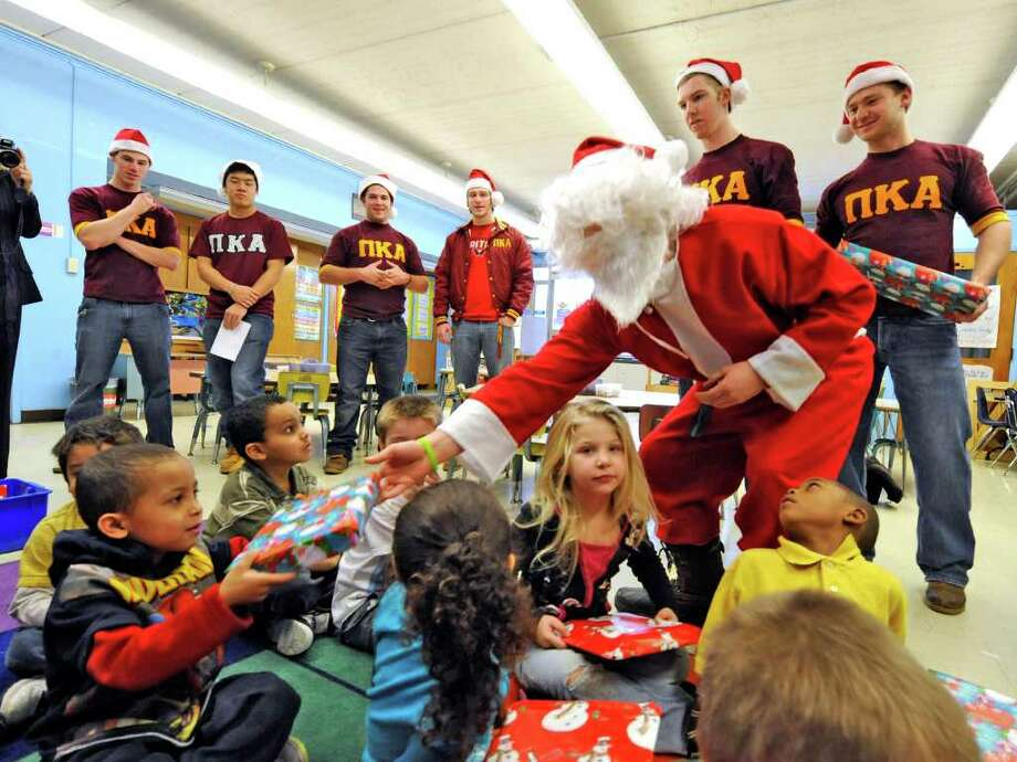 """Santa,"" played by Greg Vernon, with members of the Pi Kappa Alpha fraternity from RPI take gifts to the students of Troy's Public School 2 on December 13, 2010.   (Skip Dickstein / Times Union) Photo: SKIP DICKSTEIN / 00011385A"