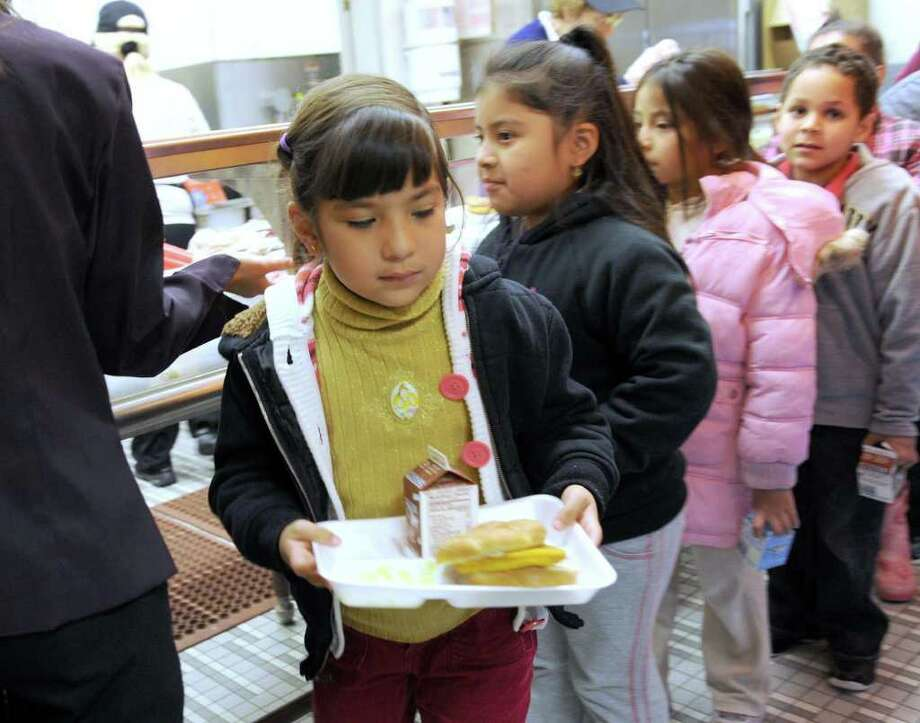 Ana Alvarez, 7, followed in line by Jessica Yunganaula, 7 and Jennifer Diaz, 6, get their lunch Monday in the cafeteria at Morris Street School in Danbury. Photo taken Monday, Dec. 13, 2010. Photo: Carol Kaliff / The News-Times