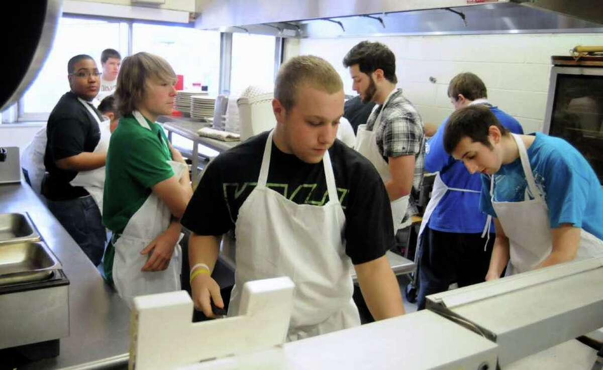 Danbury High School students in the culinary arts training class on Wed. Dec. 8, 2010 prepare several meals and then taste-test them. Chris Gmitter, 17, center, works at a station preparing rolls for linguisa chabatta.