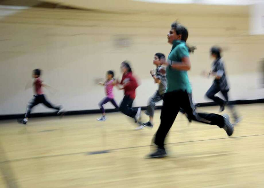 Ellen Nelson, 9, of New Lebanon School, center, taking the President's Fitness Test at the YMCA of Greenwich on Monday, Dec. 13, 2010. Photo: Helen Neafsey / Greenwich Time
