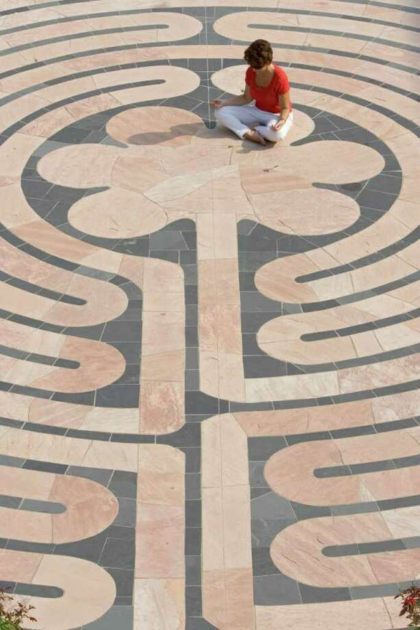 Elaine Pyle, a 43-year-old theology major, walks and meditates in a labyrinth installed on the campus of University of St. Thomas campus Tuesday, July 18, 2006, in Houston.  Pyle said she comes to meditate in the labyrinth daily. (Photo by Brett Coomer / Houston Chronicle) Contact: Elaine Pyle (281) 397-9219 h (216) 832-2379 c Photo: BRETT COOMER, STAFF / Houston Chronicle