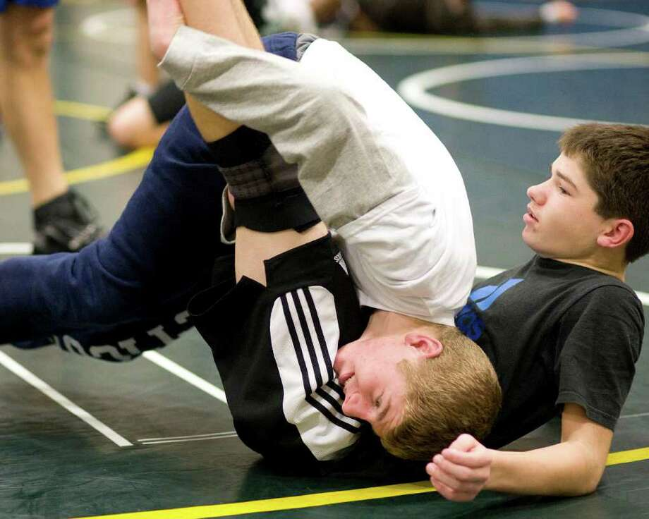 New Milford's Conor Kirkegard, top, works out with Louis Alhage at practice Monday at New Milford High. Photo: Barry Horn / The News-Times Freelance