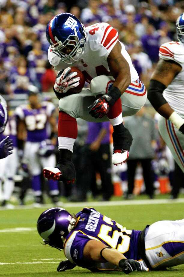 New York Giants running back Ahmad Bradshaw (44) leaps over Minnesota Vikings linebacker Chad Greenway (52) in the first half of the NFL football game at Ford Field in Detroit, Monday , Dec. 13, 2010. (AP Photo/Rick Osentoski) Photo: AP