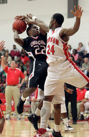 Churchill's William Huguley drives on Trent Matthews of Judson in last week's Rockets win. Photo: Kin Man Hui/Express-News
