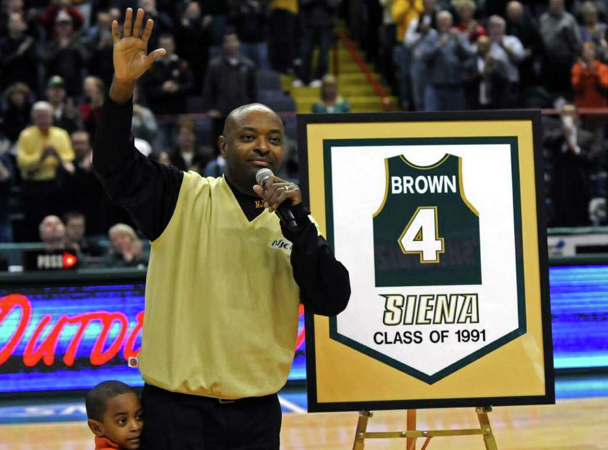 Former Siena star point guard Marc Brown, who graduated in 1991, acknowledges the crowd, along with his son Marc, Jr., 5, as his number was retired during a ceremony at halftime of the Saints' 72-69 victory over Florida Atlantic at Times Union Center. ( Philip Kamrass / Times Union )
