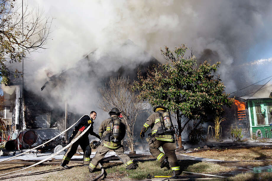 A San Antonio firefighter waits for water at a two-structure fire in the 200 block of St. John on the East Side, Dec. 13, 2010. (Jerrry Lara/glara@express-news.net)