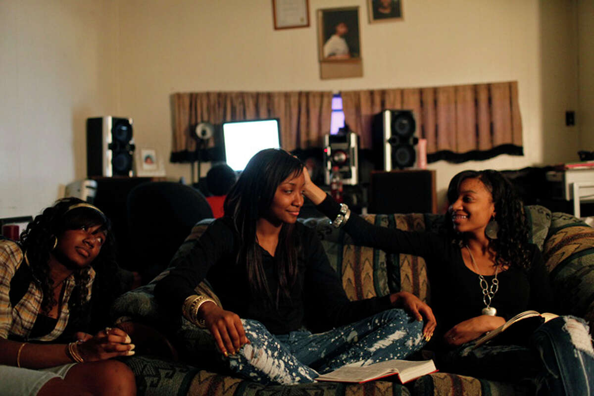 Taneva Pitts, 18, center, with her sisters, Tiffany Pitts, 17, left, and Brittany Pitts, 16, right, spends a Saturday evening with her family during the weekly bible study held at their home in San Antonio on Saturday, January 23, 2010. At the conclusion of the bible study, Teneva's father, Randy Davies, led a special prayer for their upcoming kidney transplant.