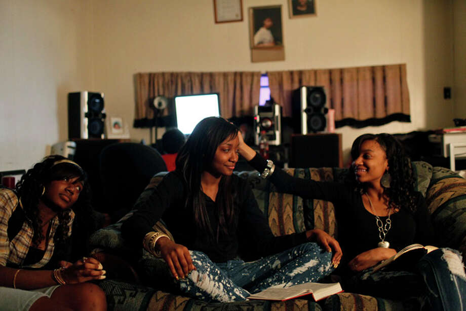 Taneva Pitts, 18, center, with her sisters, Tiffany Pitts, 17, left, and  Brittany Pitts, 16, right, spends a Saturday evening with her family  during the weekly bible study held at their home in San Antonio on  Saturday, January 23, 2010. At the conclusion of the bible study,  Teneva's father, Randy Davies, led a special prayer for their upcoming  kidney transplant. Photo: Lisa Krantz / Express-News / SAN ANTONIO EXPRESS-NEWS