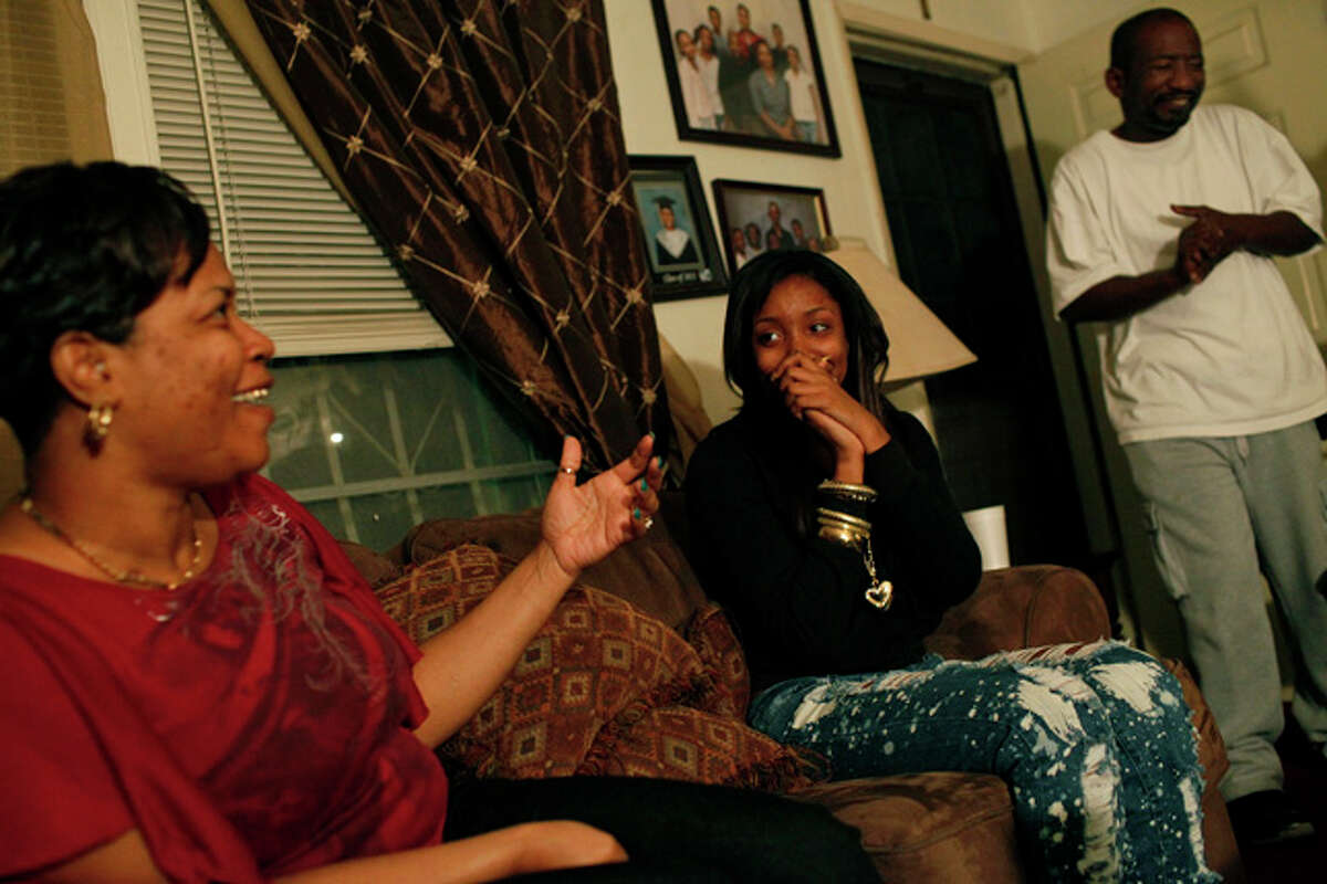 Taneva Pitts, 18, center, laughs with her mother, Andrea Pitts, left, and her uncle, Larry Davies, right, after the weekly bible study at their home in San Antonio on Saturday, Jan. 23, 2010. Davies and Teneva's father and his brother, Randy Davies, have both struggled with kidney disease and dialysis for years.