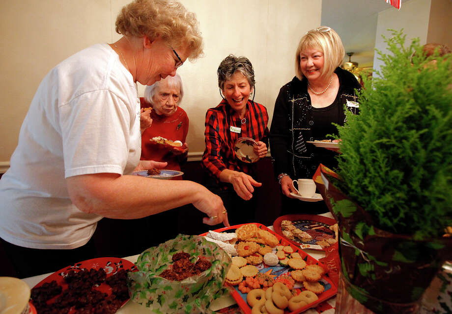 Frances Caldwell (second from right) reaches for a baked treat from Donna Nelson (from left) as guests Wendy Campbell and Kathy Wilson join the conversation. Caldwell has hosted a cookie exchange with family and friends at her home near Boerne for more than a decade. Nearly 20 women attended the exchange; each brought eight dozen cookies to taste and swap. PHOTOS BY KIN MAN HUI / EXPRESS-NEWS