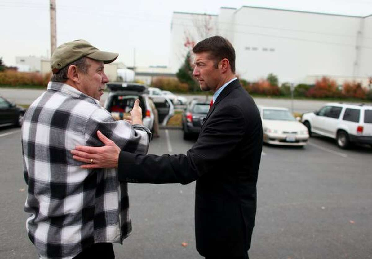Snohomish County Executive Aaron Reardon talks with Boeing Machinist Charlie Grieser outside the union hall in Everett after announcing that Boeing's second 787 production line will be going to South Carolina.