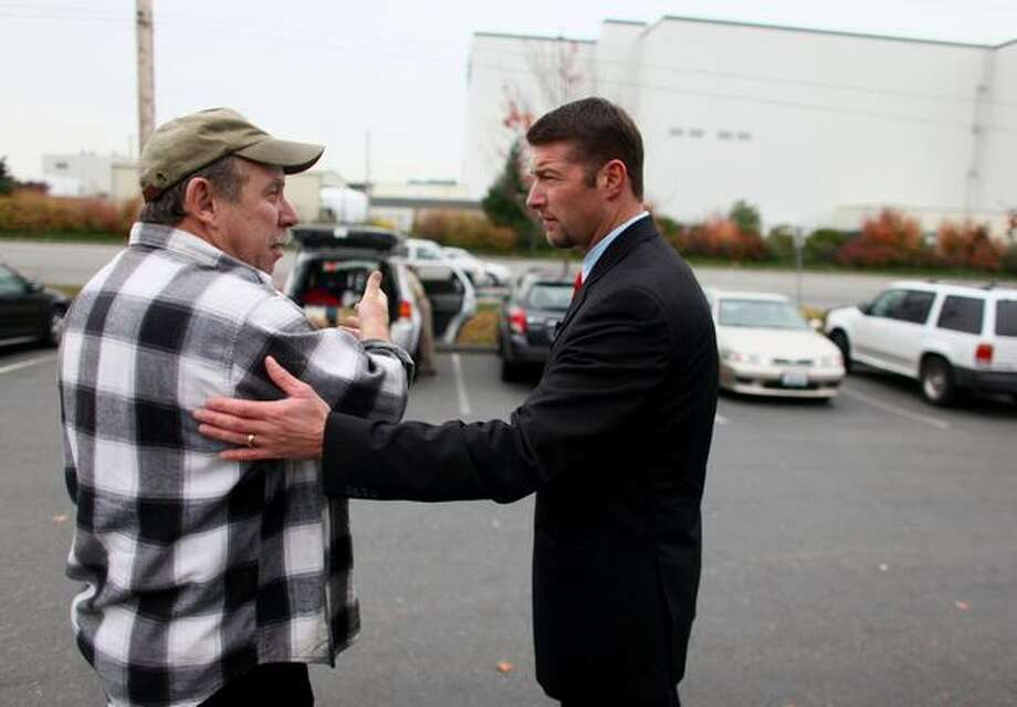 Snohomish County Executive Aaron Reardon talks with Boeing Machinist Charlie Grieser outside the union hall in Everett after announcing that Boeing's second 787 production line will be going to South Carolina. Photo: Joshua Trujillo/Seattle Post-Intelligencer
