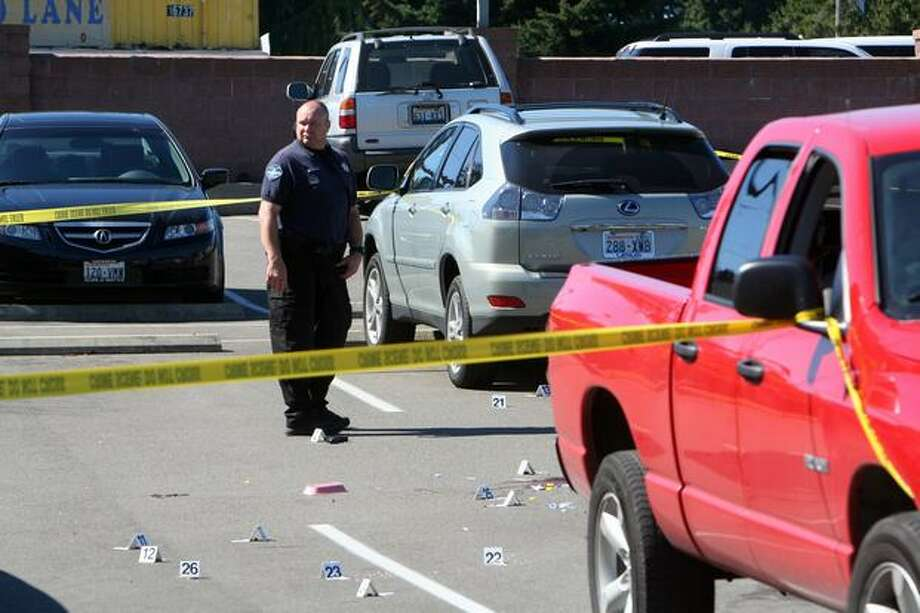 An officer stands next to a gun dropped by one of the suspects in the Hollywood Casino parking lot in Shoreline. Photo: Casey McNerthney/seattlepi.com