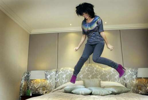 In this photo taken Nov. 9, singer Katy Perry jumps on a bed ahead of an interview with The Associated Press at a central London hotel. (AP Photo/Joel Ryan) Photo: / Associated Press