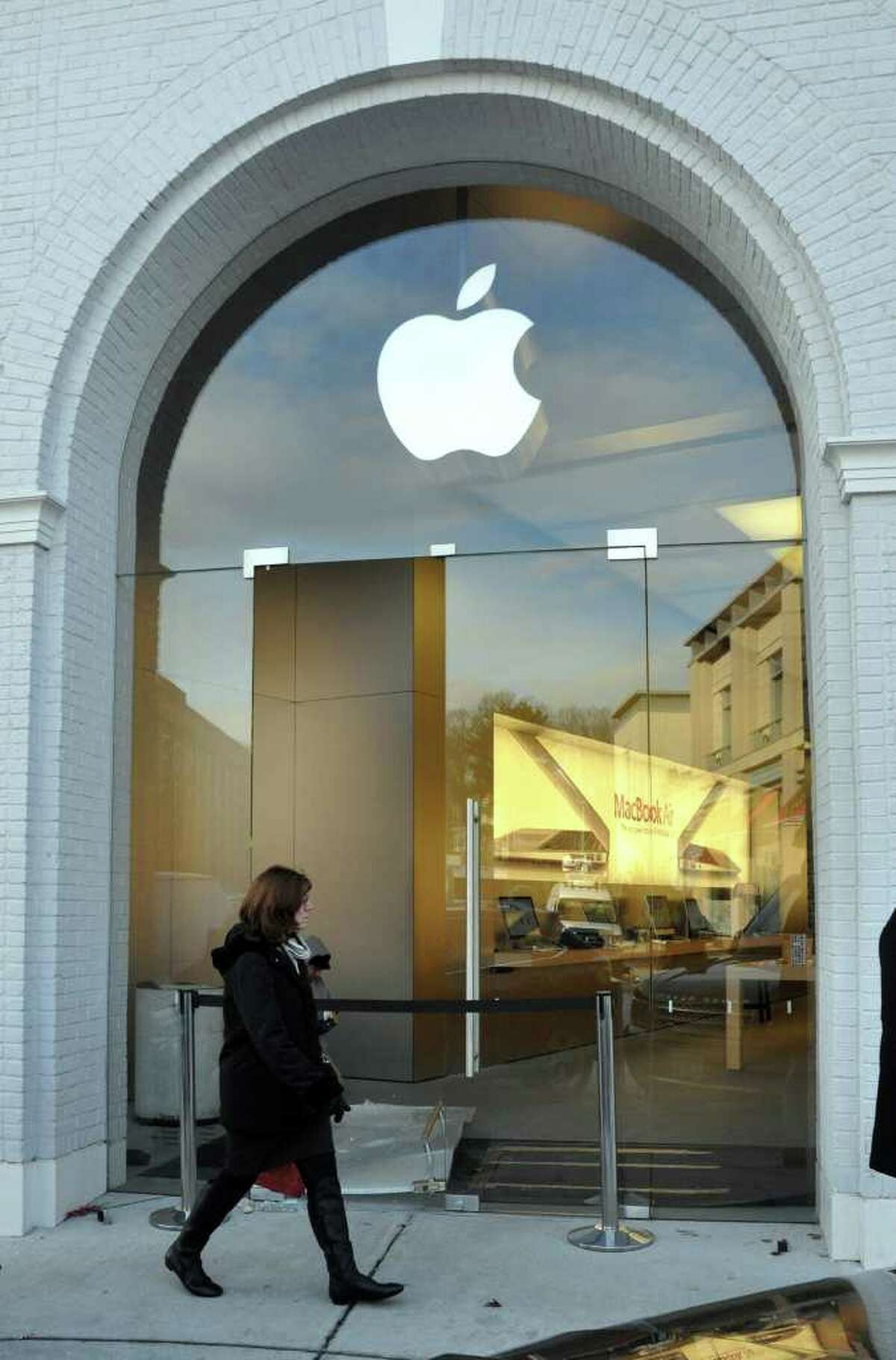 A woman walks by the broken glass door, signs of a robbery that occurred around 3a.m., at the Apple Store on Greenwich Avenue on Tuesday, Dec. 14, 2010.