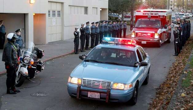 Seattle Police and Fire Department personnel salute as Medic One arrives at the Bonney-Watson Funeral Home on Capitol Hill with the body of officer Timothy Brenton. Photo: Thom Weinstein/seattlepi.com