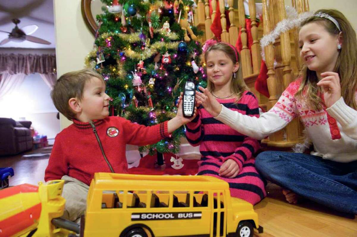 Justin, 3, Vanessa, 7, and Paulina Romano, 9, share a call from Santa Claus at their family home in Stamford, Conn. Tuesday evening December 14, 2010. Stamford Recreation Services sponsored the program to connect local children with Santa.