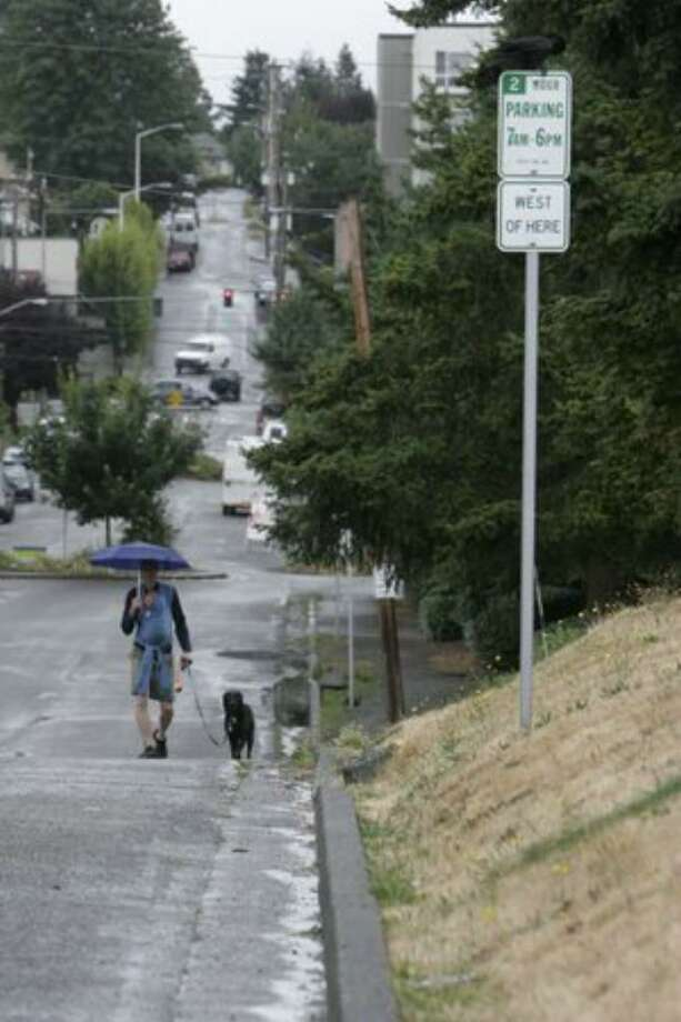 A father and son walk with their dog westbound along Northwest 87th Street in Seattle in this 2008 file photo. There are very few sidewalks in this area around Greenwood. Photo: / P-I File