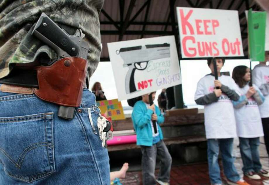 Greg Dement, of Kent, shows his opposition to gun-control advocates by wearing a Colt 1911 during a press event at Victor Steinbrueck Park organized by Washington CeaseFire, the Brady Campaign to Prevent Gun Violence, and Washington State Million Mom March. Organizers of the event hope to pressure Starbucks into adopting a no-guns policy in all its stores. Photo: Joshua Trujillo/seattlepi.com