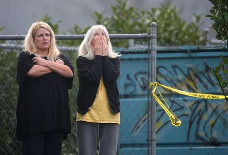 Trudie Overby, left, and her mother, Lee Stanley, watch events unfold on Sunday near the scene where four Lakewood Police officers were killed as they sat in a coffee shop near McChord Air Force Base. The women live in an apartment building next to the scene. | Photo gallery Photo: Joshua Trujillo/seattlepi.com