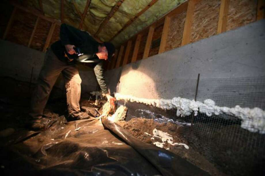 Alan Smith looks at the foundation in the crawl space of his Greenwood home on Tuesday. His home and part of the neighborhood were built on top of a peat bog that is slowly draining and sinking. The sinking earth has left the foundation of his home above ground, resting on piles. Photo: Joshua Trujillo/seattlepi.com