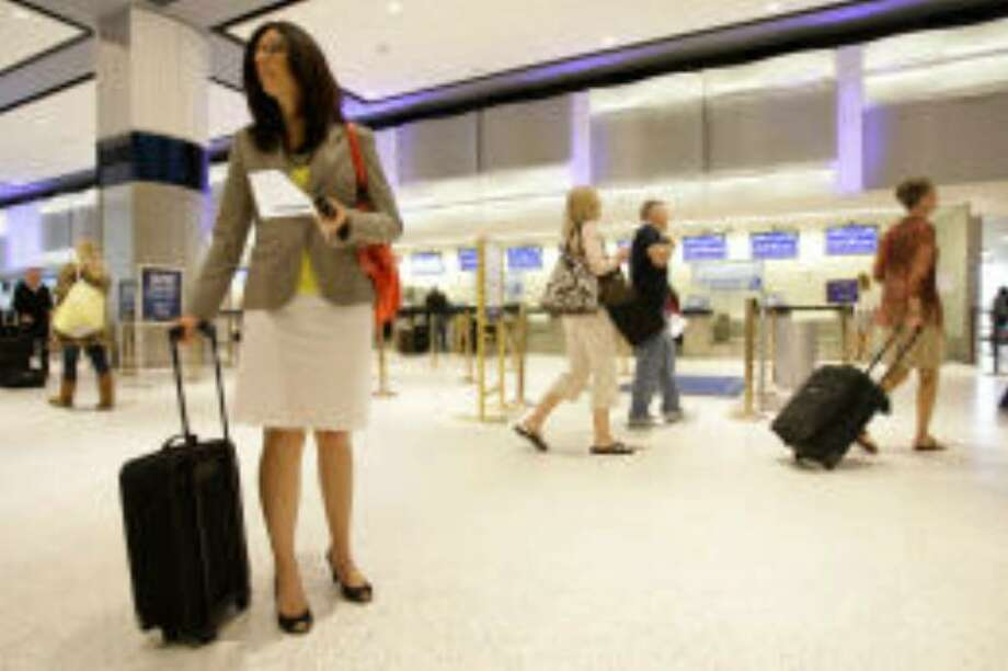 """Jessica Jackson, a teacher, has taken a different approach since airlines began adding fees for luggage. """"I wasn't used to being a light packer, but you can adjust some things,"""" she said at Bush Intercontinental Airport while en route to Boston. Photo: Melissa Phillip/Houston Chronicle"""