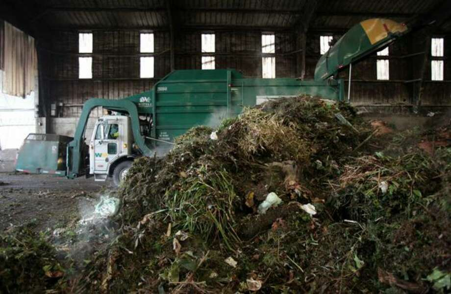 A truck delivers yard waste and food scraps collected from King and Snohomish counties into the Tipping Building at Cedar Grove's composting facility in north Everett on Wednesday. The piles of compostable material steam as they generate heat and begin the composting process. Nick Harbert of Cedar Grove says the process is initially sped up this time of year because of grass clippings added to the mix by homeowners. Photo: Joshua Trujillo/seattlepi.com