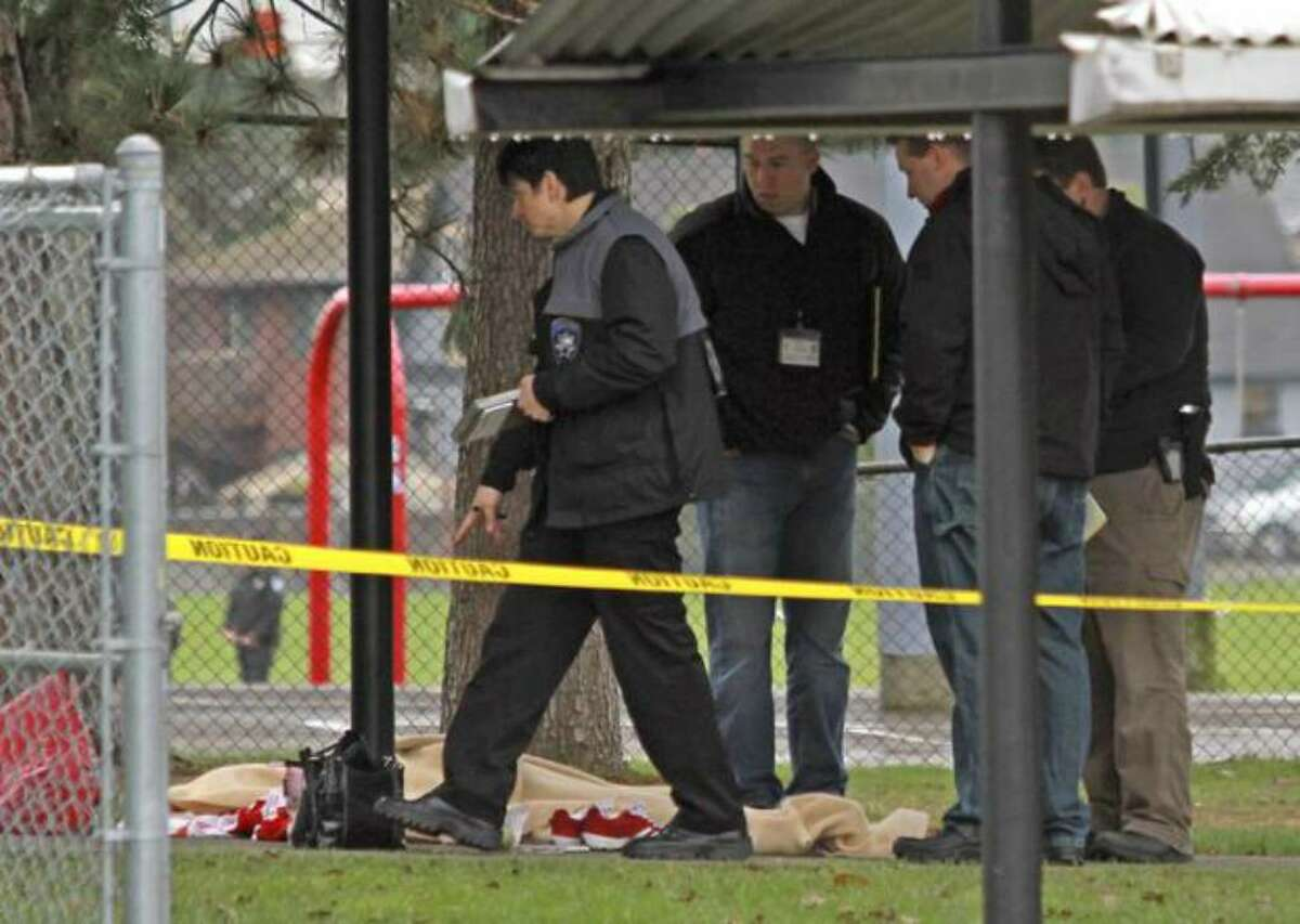 Tacoma Police officers investigate the slaying of special education teacher at Birney Elementary School in Tacoma. The suspect in the shooting was fatally shot by Pierce County sheriff's deputies shortly after. (AP Photo/The News Tribune, Dean J. Koepfler)