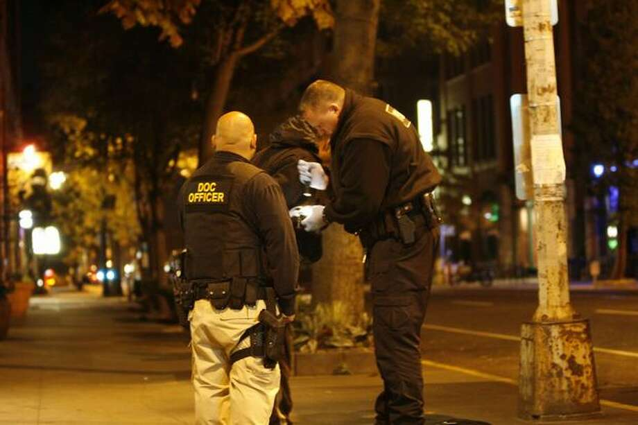 Christopher Salindron, left, and Kris Rongen with the Department of Corrections stop a man in the 2300 block of First Avenue last month in Seattle. The man was found with heroin and arrested before 5 a.m. Photo: Casey McNerthney/seattlepi.com