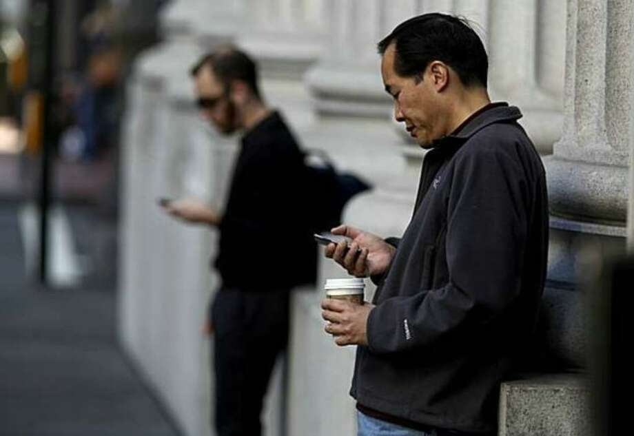 Orthopedic doctors are increasingly seeing injuries from people using smartphones, mainly from people slumping over to use the devices. Photo: / San Francisco Chronicle