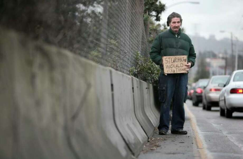"A man, who asked that his name be withheld, holds a sign while panhandling on the North 45th Street onramp to Interstate 5 on Wednesday. ""People judge you right away when they see you out here. They have no idea what we went through to get here,"" he said. ""I don't like to be out here. I don't actually make much money."" Photo: Joshua Trujillo/seattlepi.com"