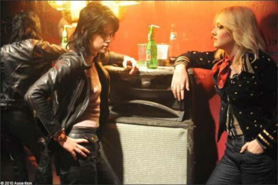 "Kristen Stewart, left, as Joan Jett and Dakota Fanning as Cherie Currie in ""The Runaways."""