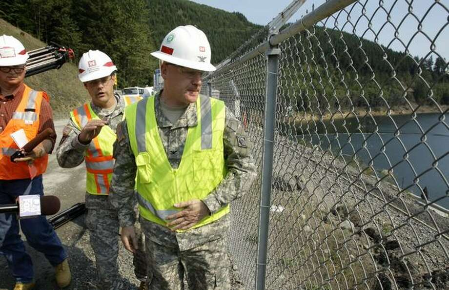 In this Sept. 23 photo, Col. Anthony Wright, right, and Lt. Col. James Rollins, second from right, look down at the Howard Hanson Dam as they talk to reporters. (AP Photo/Ted S. Warren) Photo: / Associated Press