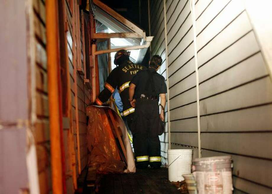 Seattle fire investigators examine the scene of a Nov. 8 arson behind Moonphoto in the 7700 block of Greenwood Avenue North. The Nov. 8 fire continues a string of Greenwood arsons. Photo: Casey McNerthney/seattlepi.com