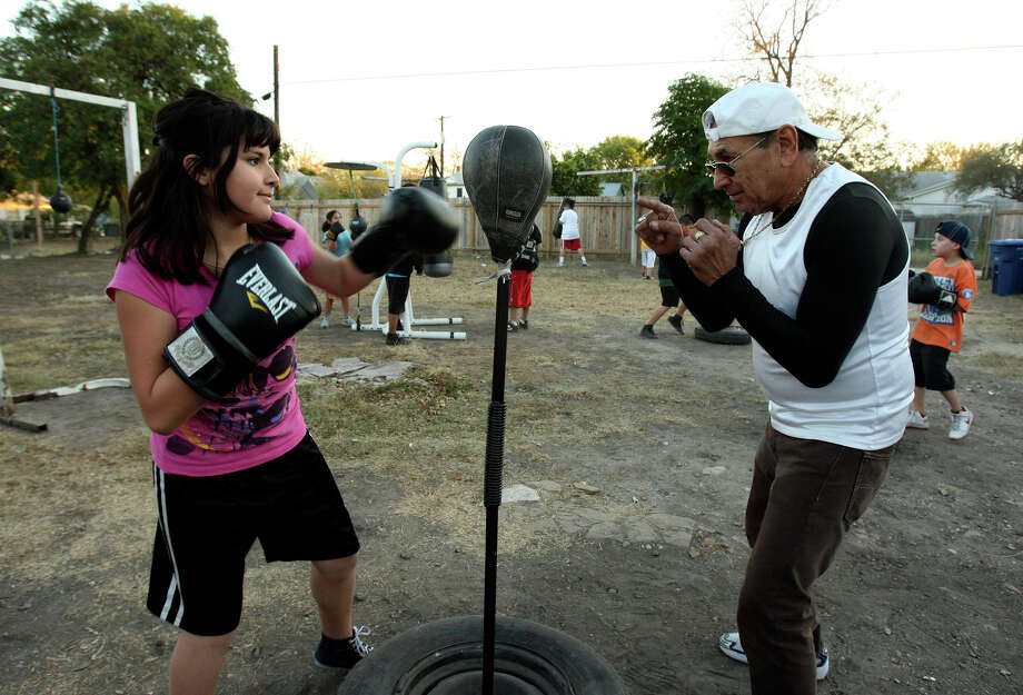 Former boxer Charlie Mata works with a student in the Advocates Youth Boxing Program. About 600 youths have gone through the program, which began in 1999. Photo: Helen L. Montoya/Express-News
