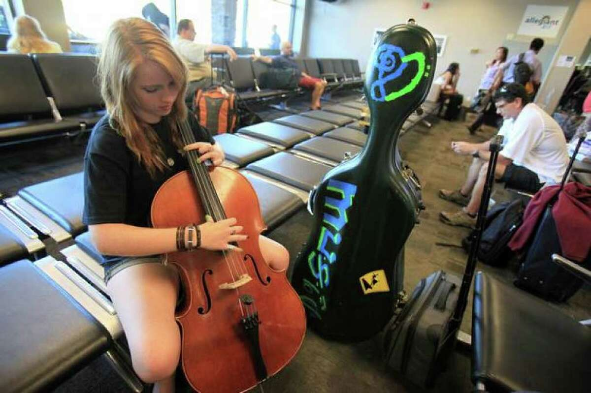 Sedona Wargo, 16, plays her cello while traveling to Canada for a music festival on Thursday. Wargo used the small Whatcom County airport to travel from her Arizona home because of convenience and the price of her ticket.